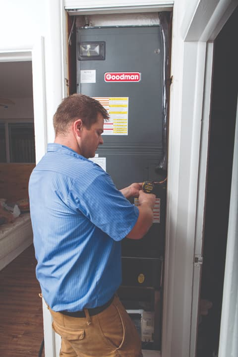 Image: Air Conditioning Technician testing an electrical box.